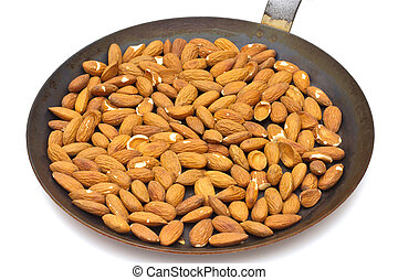 Pan with roasted almonds on white background