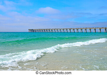 Panama City, FL, beach, white sand and ocean waves with a pier