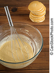 Pancake or flapjack mixture batter with cakes in background