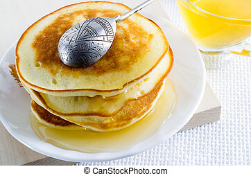 Pancake with honey and silver spoon on a white plate