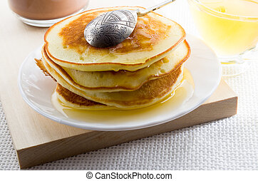 Pancake with honey and vintage silver spoon on a white plate