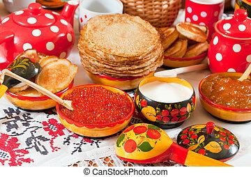 Pancake with red caviar and tea during Pancake Week