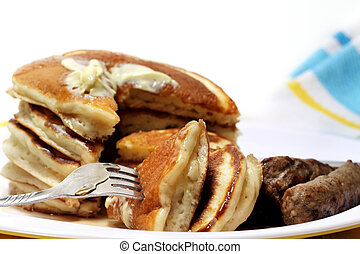 Hearty breakfast of pancakes and sausage with butter and syrup