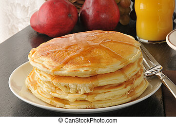 Closeup of hot pancakes with syrup and a glass of orange juice