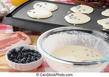 Pancakes cooking on the griddle - A bowl of blueberrry ...