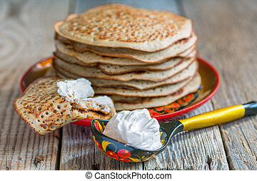 Pancakes from wholemeal flour and spoon sour cream.