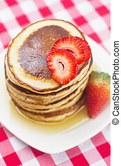 Pancakes, honey and strawberry on checkered fabric