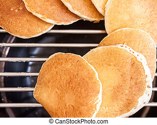 Pancakes isolated on grill - Small pancakes isolated on the ...