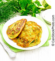 Pancakes of zucchini on light wooden board - Fritters of ...