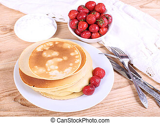 pancakes on a plate with berries and cream
