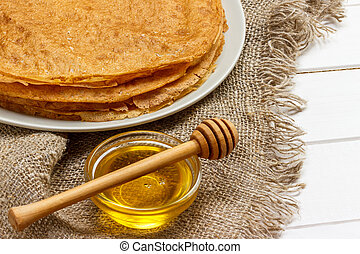 Pancakes on a white plate. Fresh honey in a jar. Wooden spoon for honey. Dessert. Healthy Breakfast. The table was covered in burlap