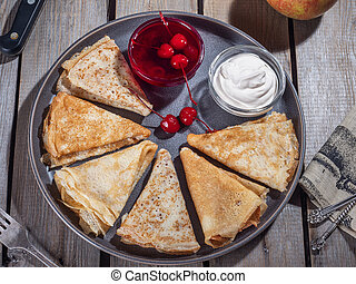 Pancakes rolled up in a big gray plate with a triangle, near...