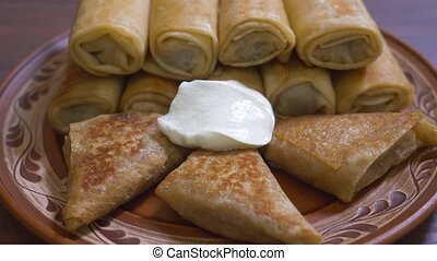 Pancakes rolled up with sour cream. Pancakes stuffed with sour cream, a wooden spoon with sour cream. Close-up, rural style.