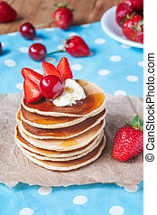 Pancakes traditional homemade breakfast or lunch with strawberry, honey and butter in white dish