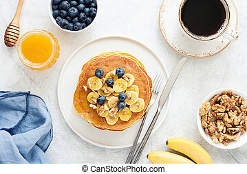 Pancakes with banana, blueberry and cup of coffee, tasty breakfast