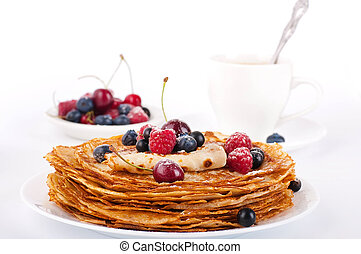Pancakes with berries and cup of coffee on a white background