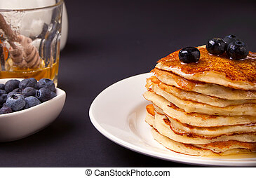 Pancakes with berries and honey on the black background