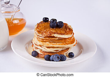Pancakes with berries and honey on the white background