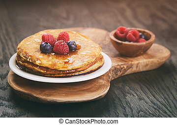 Pancakes with berries on wood table