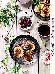 pancakes with berries on wooden table.