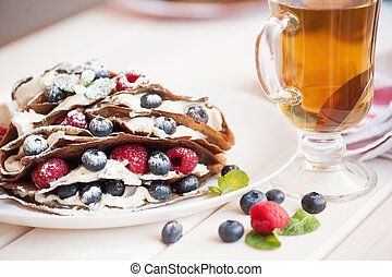 Pancakes with blueberries and raspberries, mascarpone cream and tea