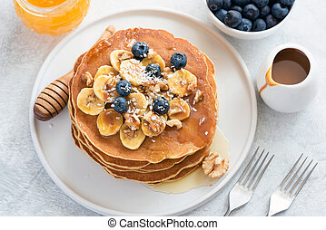 Pancakes with blueberries, banana, walnuts and honey on white plate