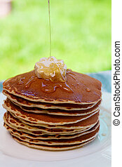 Pancakes with butter and honey on white plate on in garden or on nature background. Maple syrup pouring on pancakes stack.