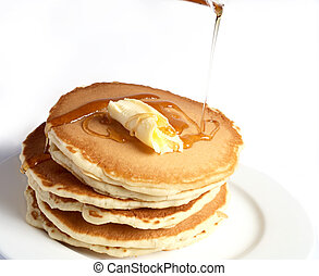 A pile of pancakes with a dollop of butter and maple syrup being poured over them