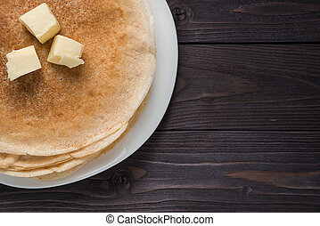 pancakes with butter on a wooden background