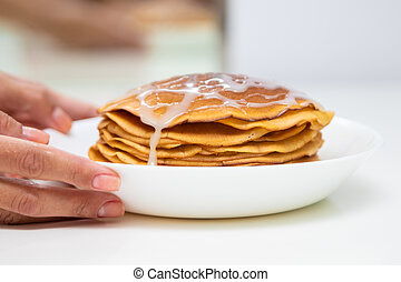 Pancakes with condensed milk on a white light background. A stack of pancakes with sweet sauce. Hands serve pancakes. Close up view.
