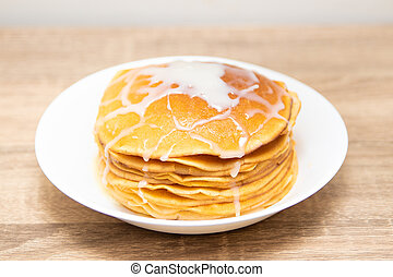 Pancakes with condensed milk on a white light background. A stack of pancakes with sweet sauce. Close up view.