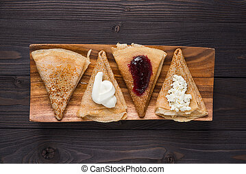 pancakes with filling on a wooden background