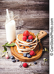 Pancakes with fresh summer berries and bottle of milk