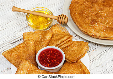 pancakes with honey and jam on wooden background