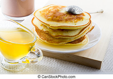 Pancakes with honey and vintage silver spoon on a white plate
