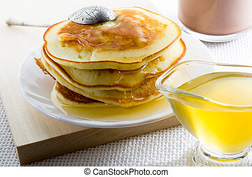 Pancakes with honey and vintage silver spoon