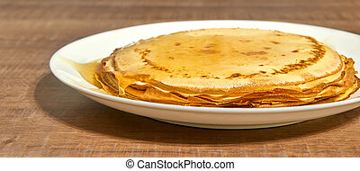 Pancakes with honey on white plate.