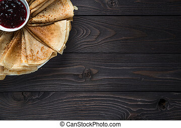 pancakes with jam on a wooden background