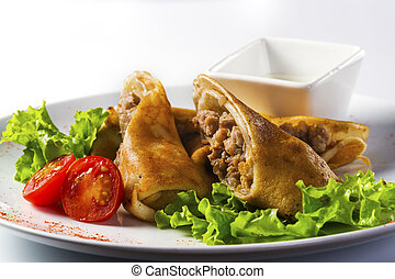 Pancakes with meat and basil on a white background