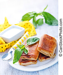 pancakes with meat and fresh basil on the plate