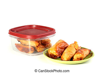 Pancakes with meat in a plate and a plastic box for storage ...
