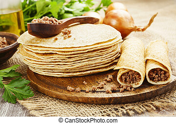 Pancakes with meat on the wooden table