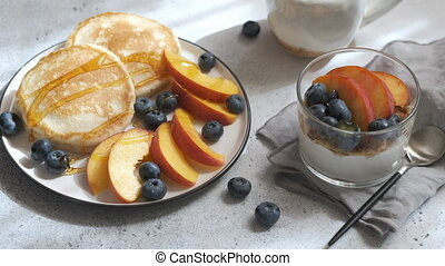 Close up of pancakes with grilled peaches, fresh blueberry and maple syrup.