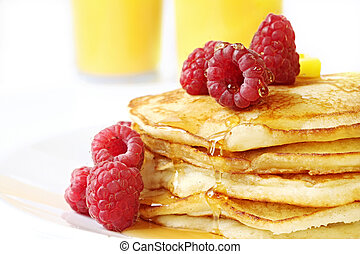 Pancake stack with fresh raspberries, maple syrup and butter. Orange juice behind. A delicious indulgent breakfast.