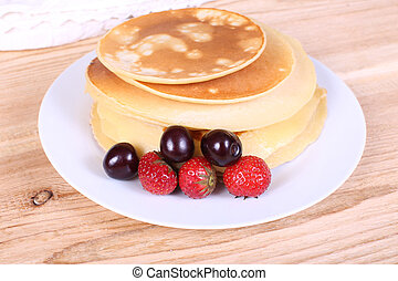pancakes with ripe berries. on a wooden table.