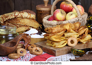 Pancakes with sour cream and apples on a wooden table. Carnival