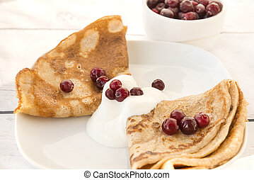 pancakes with sour cream and cranberries on a plate
