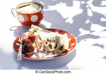 Pancakes with strawberries and cup of coffee