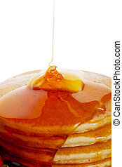 Hot buttered pancakes with maple syrup drizzling down onto the stack.