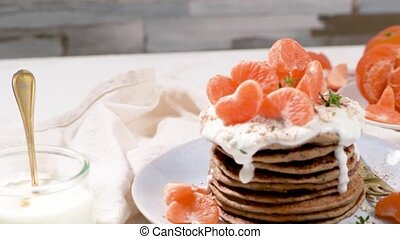 Pancakes with yogurt and tangerines on a light modern kitchen counter top with oat, thyme and mint leaves.